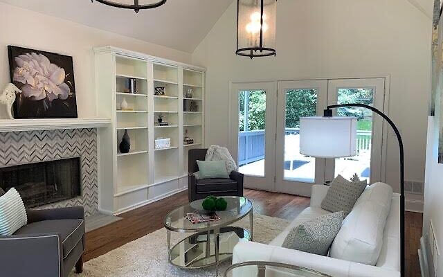Less crowded bookshelves in this staged living room gives the prospective buyer a sense that there will be plenty of room for his or her own collectables.