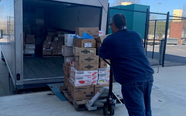 Second Helpings Delivery and Fleet Operator Enzo Albana Galateo Campos loads a pallet of food from Coolray Field last month.