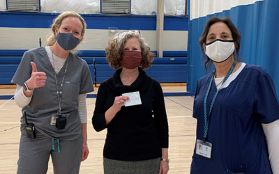 Two Epstein School nurses Jessica Blatt and Joyce Tritt bookend Assistant to the Head of School Denise Gelernter, center, after she receives her vaccine.