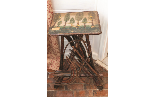 Howard collects Tramp art.  Shown here is a wooden table in the Florida room with an oil-painted tree design.