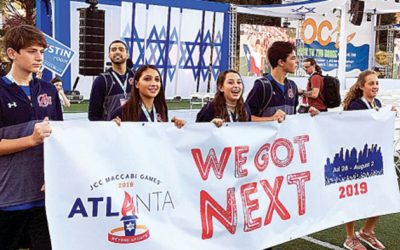 At the 2018 opening ceremonies, Atlanta athletes Jake Francombe, Jordan Starr, Hailey Rubin, Jake Powers, and Barri Seltz carry a banner showcasing Atlanta as the next year's host.