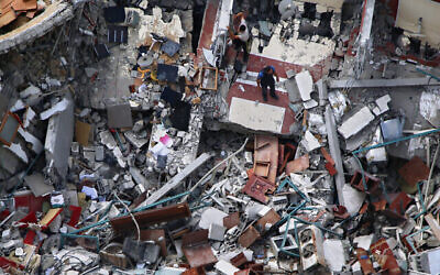 Palestinians inspect the destroyed building housing the offices of The Associated Press and other media after it was hit last week by an Israeli airstrike, in Gaza City, Friday, May 21, 2021. Israel says the building housed Hamas offices. (AP Photo/Hatem Moussa)