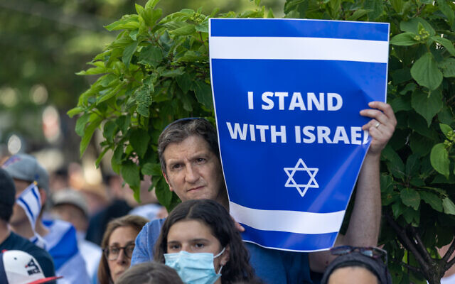 Nathan Posner for the AJT// A man holds a sign and listens to speakers at a pro-Israel rally in Atlanta.