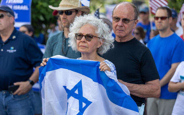 Nathan Posner for the AJT// A couple hold an Israeli flag while listening to speakers at a pro-Israel rally.
