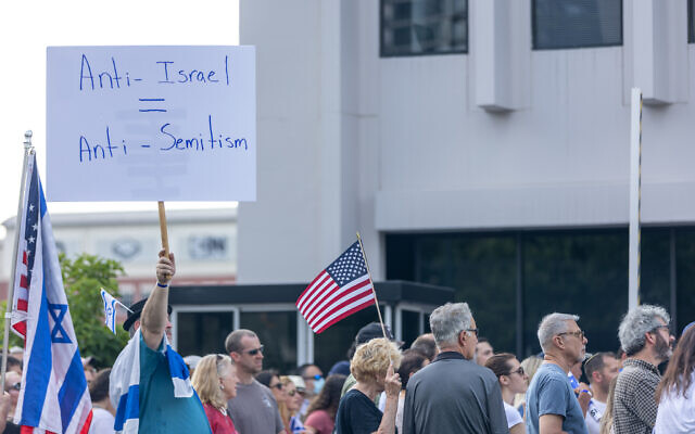 Nathan Posner for the AJT// A man holds a sign equating anti-Israelism to anti-Semitism at a pro-Israel rally.