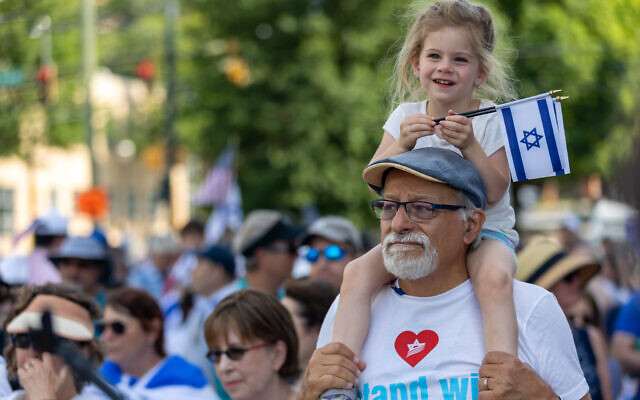 Nathan Posner for the AJT//  A young child sits on the shoulders of an older man while holding Israeli flags at a pro-Israel rally.