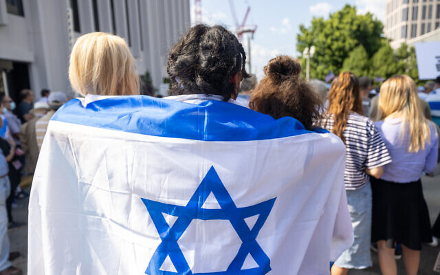 Nathan Posner for the AJT// Attendees of a pro-Israel rally wear an Israeli flag around one another.