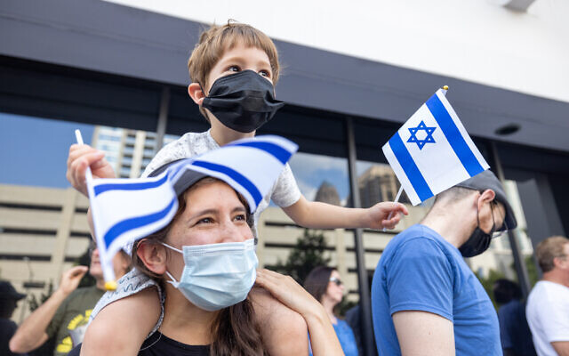 Nathan Posner for the AJT// A young supporter of Israel waves flags during a rally.