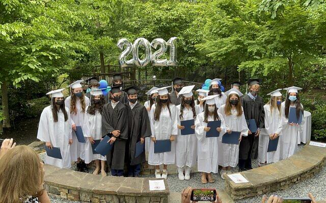 Graduates walk under the chuppah.