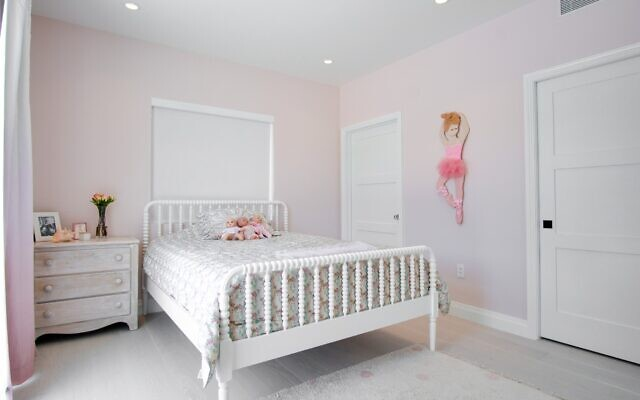 This room of Pachter's daughter has modern pink walls, white and gold contemporary light fixture with Heather's childhood bed painted white. The floral print bedspread is from Heather's childhood.