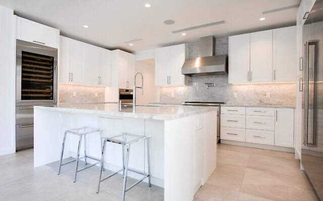 Counter and backsplash are white and gray with translucent veins of pink and green reflecting throughout the room. Brushed nickel fixtures, simple mini cans for even, bright lighting plus under-cabinet accent lights.