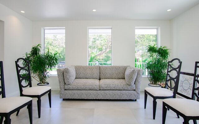 Jordan built the sitting room with updated furniture from the Rubin family by reupholstering the sofa and chairs with modern fabric. Two lush tropical plants flank the sofa and take advantage of natural light.