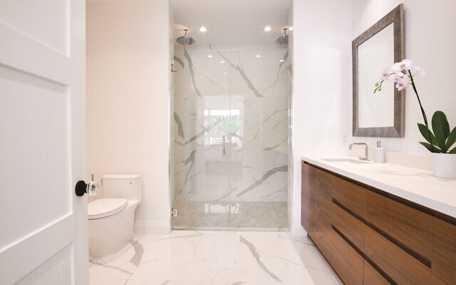 Pachter's ultra-chic master bath has large format marble-look porcelain floor tile and walls with matching Calacatta quartz countertop warmed up with a custom walnut vanity. Walk-in shower with frameless glass door, marble mosaic shower floor, double shower system on opposing walls in chrome.