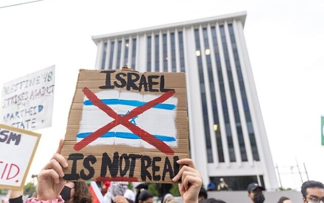 """A protestor holds a sign saying """"Israel is not real"""" during a pro-Palestine protest, with the Israeli consulate in the background. // Nathan Posner for the AJT"""