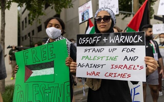 A protestor holds a sign calling for Senators Ossoff and Warnock to act on Israel during a Palestinian protest. // Nathan Posner for the AJT