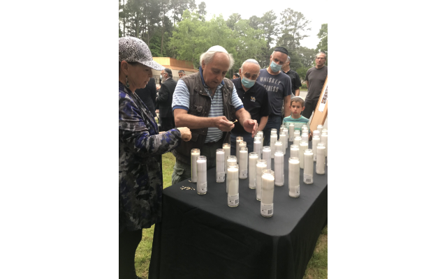 Attendees stand in line to light candles