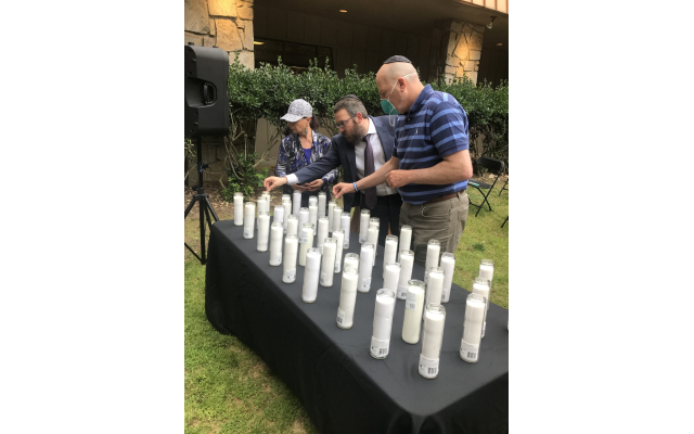 Rabbi Mendy Gurary assists in lighting candles.