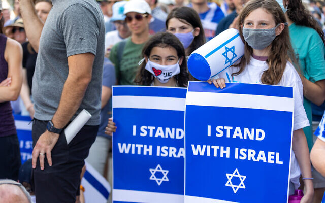 Two young girls are seen with signs at a rally for Israel.
