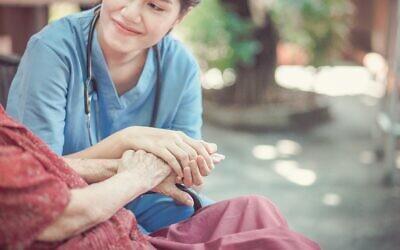 Chompoo Suriyo/Shutterstock //  Elderly woman with her caregiver at home.
