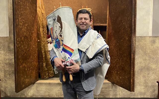 Rabbi Larry Sernovitz holds one of Kol Emeth's Torah scrolls.
