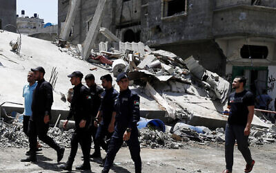Hamas police officer secure the rubble of destroyed residential building which was hit by Israeli airstrikes, in Beit Lahiya, Gaza Strip, Thursday, May 20, 2021. (AP Photo/Adel Hana)