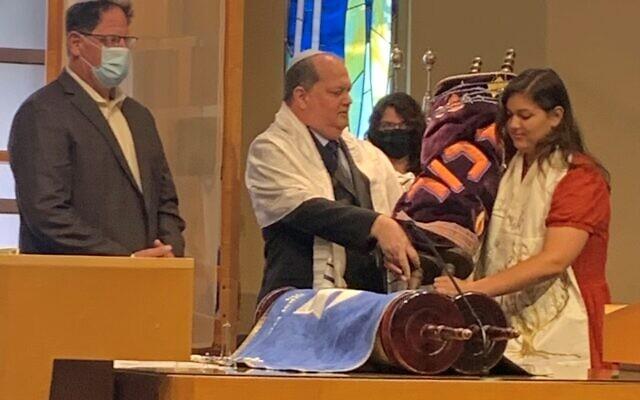Katie holds the Torah.
