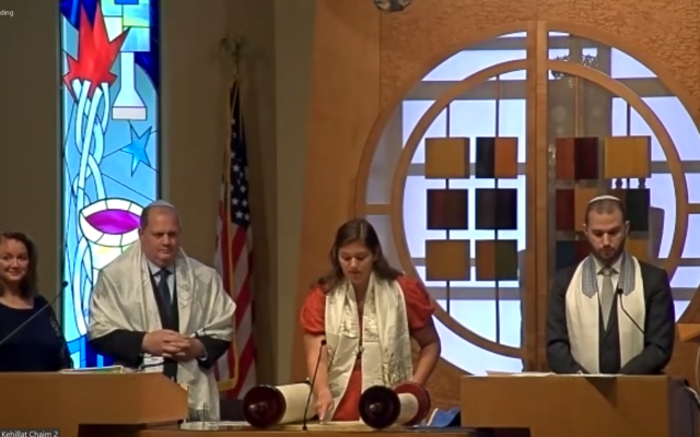 Katie Kahn reads from the Torah with parents and Rabbi Jason Holtz nearby.