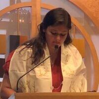 Katie Kahn on the bimah blessing the wine during Havdalah.