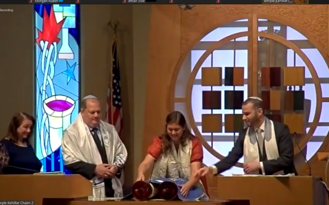 Katie uncovers the Torah scroll with her parents and Rabbi Jason Holtz.
