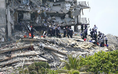 Rescue workers search in the rubble at the Champlain Towers South condominium, June 26, 2021, in the Surfside area of Miami (AP Photo/Lynne Sladky)