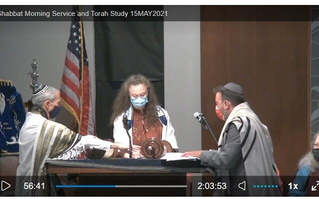 Courtesy of Temple Beth David A screenshot shows Bobby Horowitz holding scroll open as Genie Nickelsberg reads and Rabbi Jesse Charyn looks on.