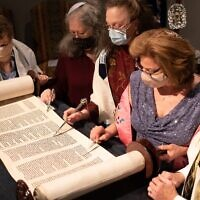 Judi Kern holds the Torah scroll open as Bobby Horowitz looks on. Shelly Pirkle, Genie Nickelsberg and Denise Whitlock read the Hebrew.