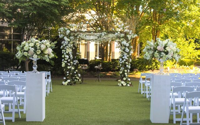 Photos by Terri Nash Photography // Revel in this white outdoor hotel wedding chuppah.