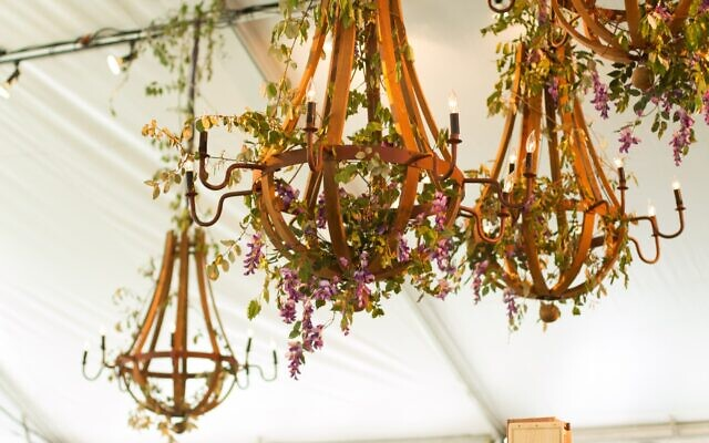 A design of fresh seasonal florals suspend from wooden chandeliers.