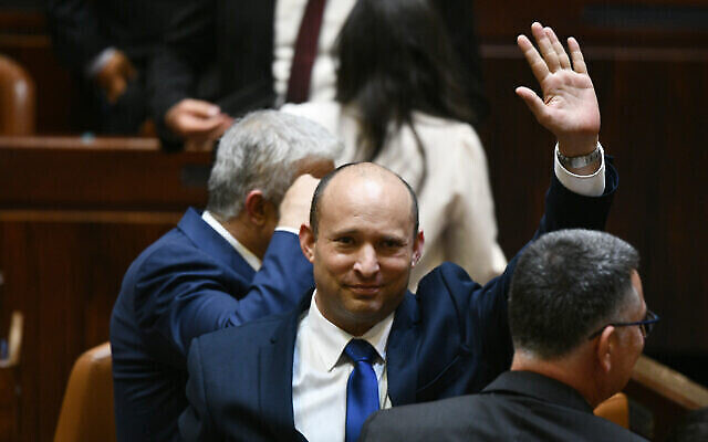 Newly elected Prime Minister Naftali Bennett waves, with Yair Lapid (left) and Gideon Sa'ar (right) alongside him, after their new coalition wins Knesset approval, June 13, 2021 (Haim Zach / GPO)