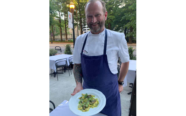 Chef Craig on the front patio displays his house-made artichoke ravioli with mushrooms.