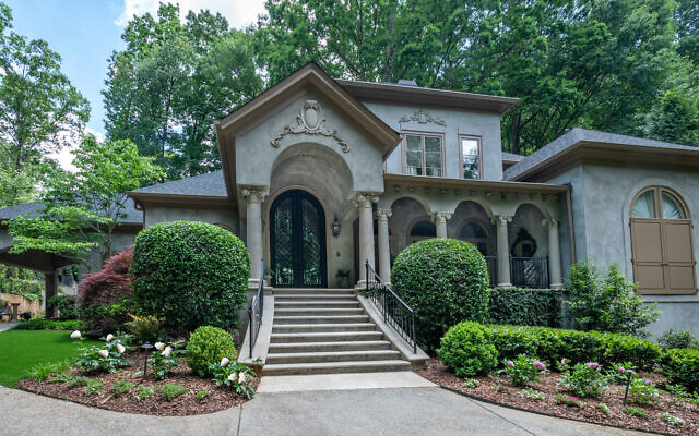 The Mediterranean Brookhaven home has 7,000 square feet with front yard peonies in bloom.