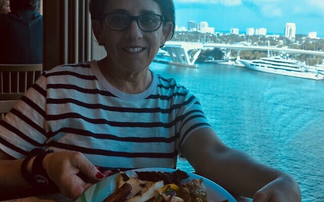 Nancy Miller enjoys lunch as her cruise departs a port.