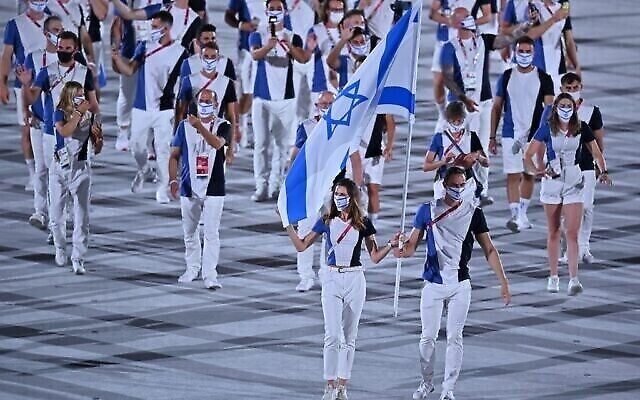 Israel's flag bearers Hanna Minenko (L) and Yakov Toumarkin lead the delegation during the opening ceremony of the Tokyo 2020 Olympic Games, at the Olympic Stadium, in Tokyo, on July 23, 2021. (Photo by Ben STANSALL / AFP)