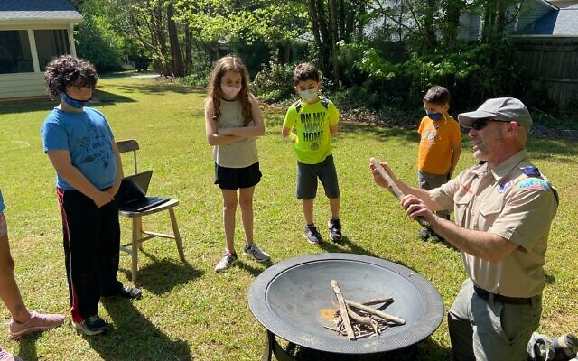 Webelos den leader (and Eagle Scout) Ben Burnstein teaches his group how to light a fire.
