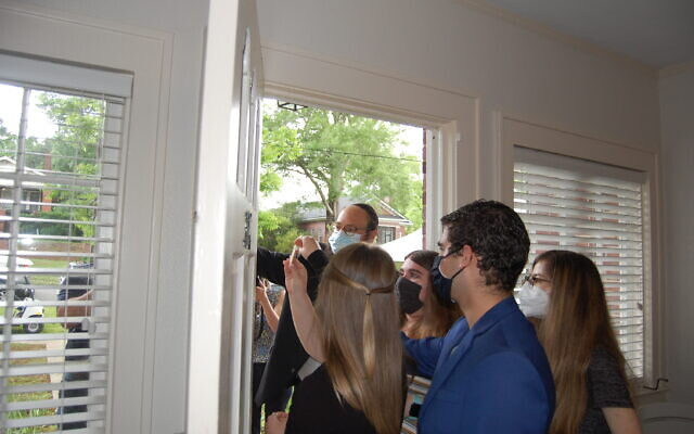 Georgia College Hillel students install a mezuzah on their newly purchased house.
