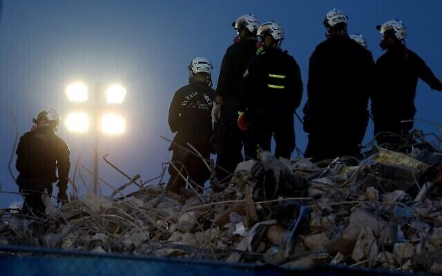 Search and rescue workers oversee an excavator dig through the rubble of the collapsed 12-story Champlain Towers South condo building on July 9, 2021 in Surfside, Florida. (Anna Moneymaker / GETTY IMAGES NORTH AMERICA / Getty Images via AFP)