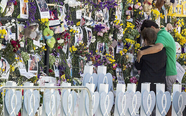 People mourn at the memorial wall for the victims of the Champlain Towers South collapse, in Surfside, Florida, on July 8, 2021. (Pedro Portal/Miami Herald via AP)
