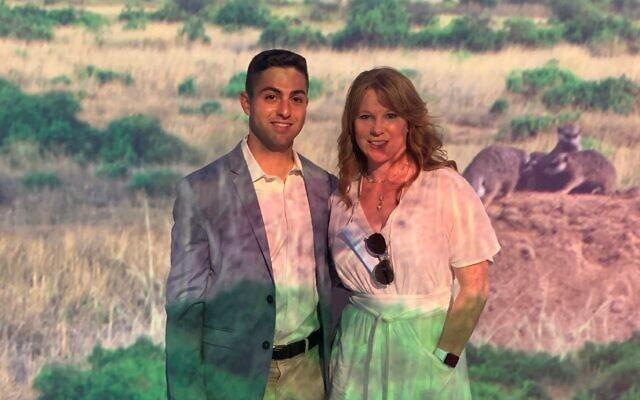 Matt Novak and Stephanie Blank pose in front of a Serengeti scene.