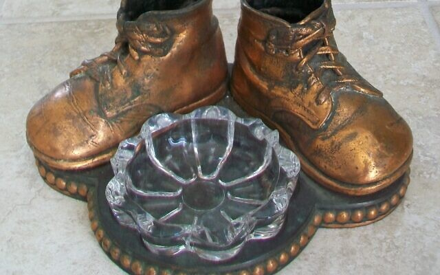 Baby shoes were a common decoration on mid-century family ashtrays.