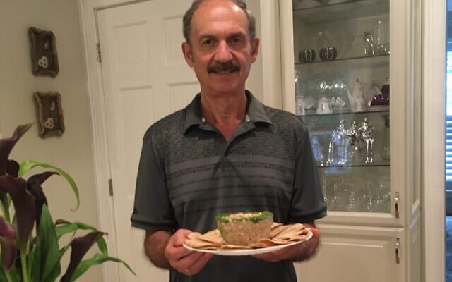 Lev Mebel holds plate of cod liver he and his wife prepared, paired with pita bread for serving.