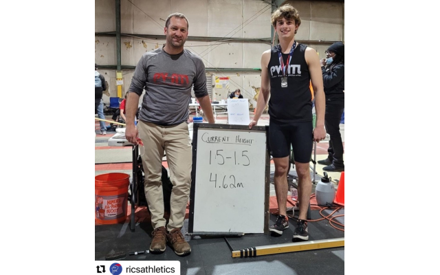"""Davis Academy track coach Matt Barry and student Nick West pose with the record of West's best performance of 15' 1.5"""". (Courtesy of Matthew Barry)"""