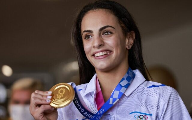 Olympic Gold medalist Linoy Ashram at Ben Gurion Airport after winning the gold medal in rhythmic gymnastics at the Olympic Games in Japan, August 11, 2021. (Menahem KAHANA // AFP/Times of Israel)