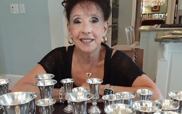 Sheryl Blatt sits with her rescued Kiddush cup collection.