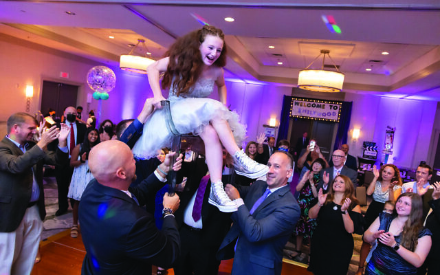 Photos by Revelry Photo House// The bat mitzvah girl is lifted up, chair and all.